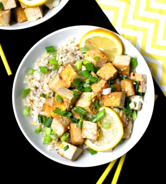 Overhead shot of a bowl of sticky glazed lemon tofu with brown rice and scallions and slices of lemon in a white bowl with yellow chopsticks.