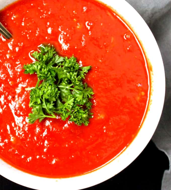 Close up of a traditional marinara sauce in a white bowl with parsley on top