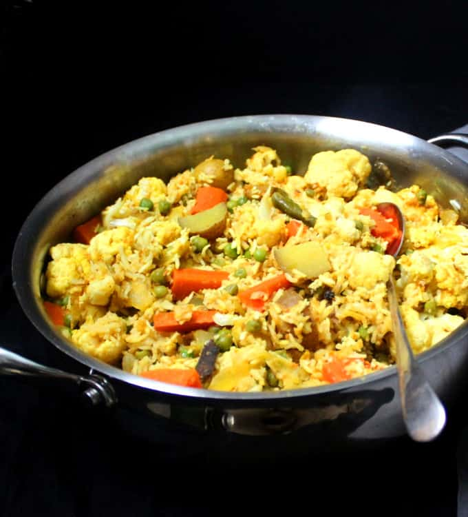 A steel pot with turmeric-stained tehri, a veg pulao made with rice, veggies and spices