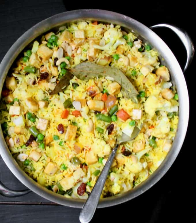 A top shot of navratan pulao in a steel pan with a spoon