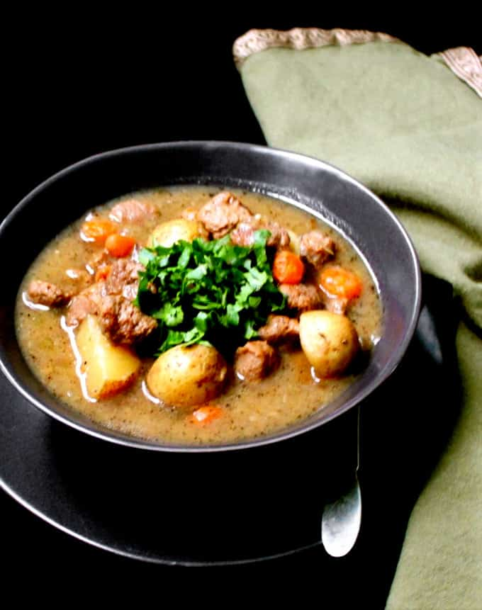 Front shot of a black bowl with vegan beef stew, parsley, carrots and potatoes