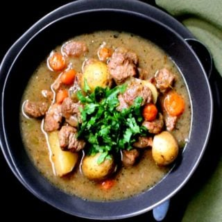 Vegan Beef Stew in a black bowl with chunks of potatoes, carrots, tvp, and celery