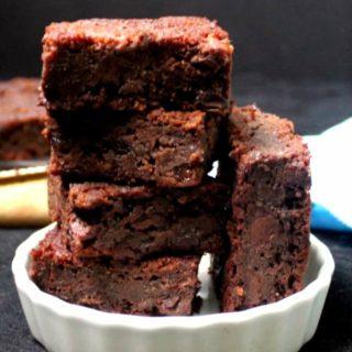 A stack of five gluten free vegan brownies in a white ramekin