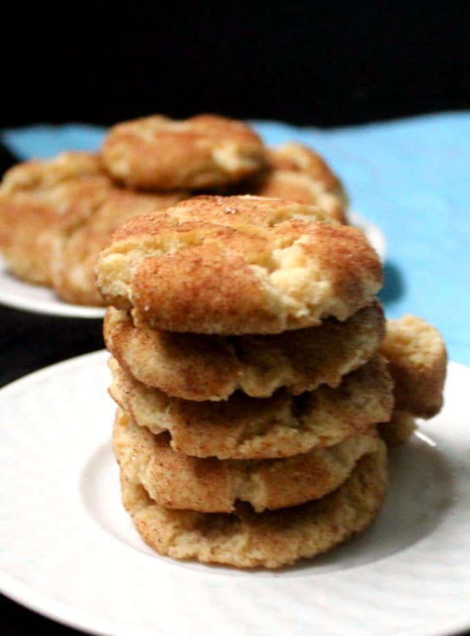 Vegan Snickerdoodle Cookies stacked on a white plate with a blue napkin in the background