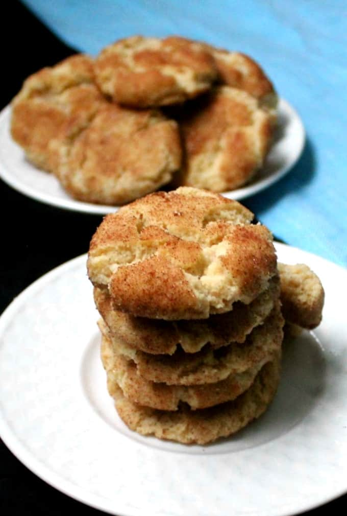 Vegan Snickerdoodles stacked on a white plate with a blue napkin