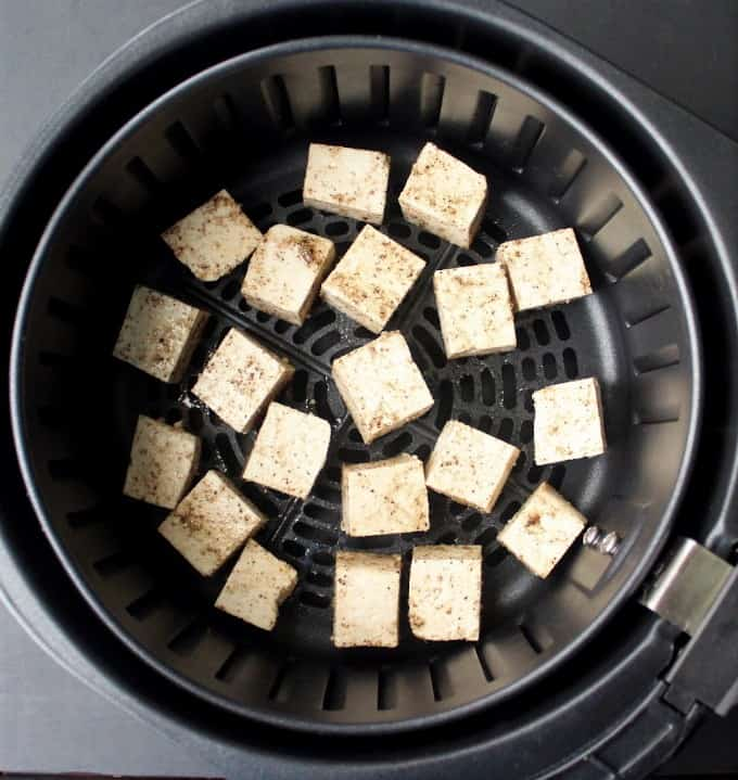 Tofu cubes arranged in an air fryer basket