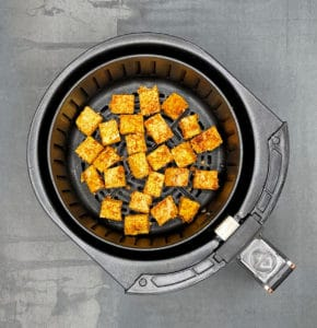 Photo of tofu cubes in air fryer basket before baking