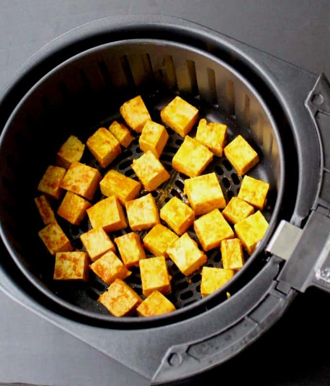 Turmeric tofu cubes in the air fryer basket