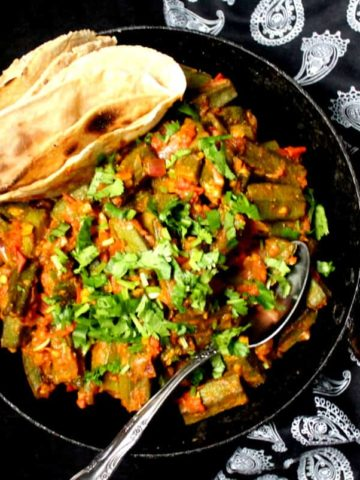 A top partial shot of a black kadhai with Bhindi Masala, Indian stir fry okra with a tomato onion sauce and spices