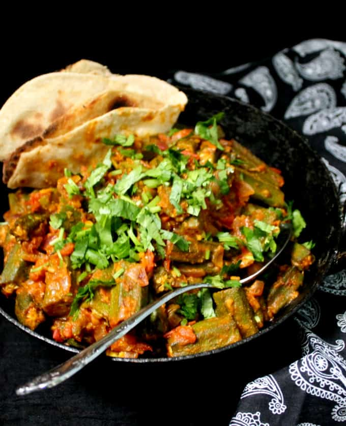 A front shot of a black kadhai with Bhindi Masala, Indian stir fry okra with a tomato onion sauce and spices and a spoon in it