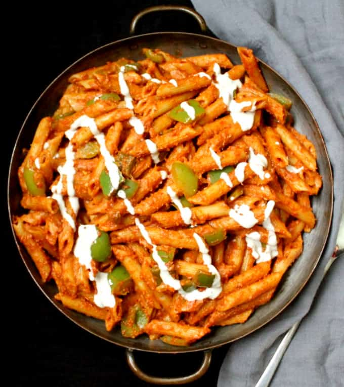 Photo of masala pasta in a copper serving bowl with gray napkin.