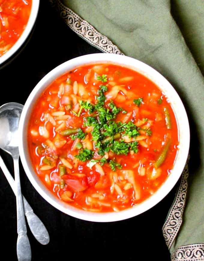 A top shot closeup of a white and black bowl with minestrone soup with orzo, beans, carrots, celery, onions, green beans and cabbage and parsley on top