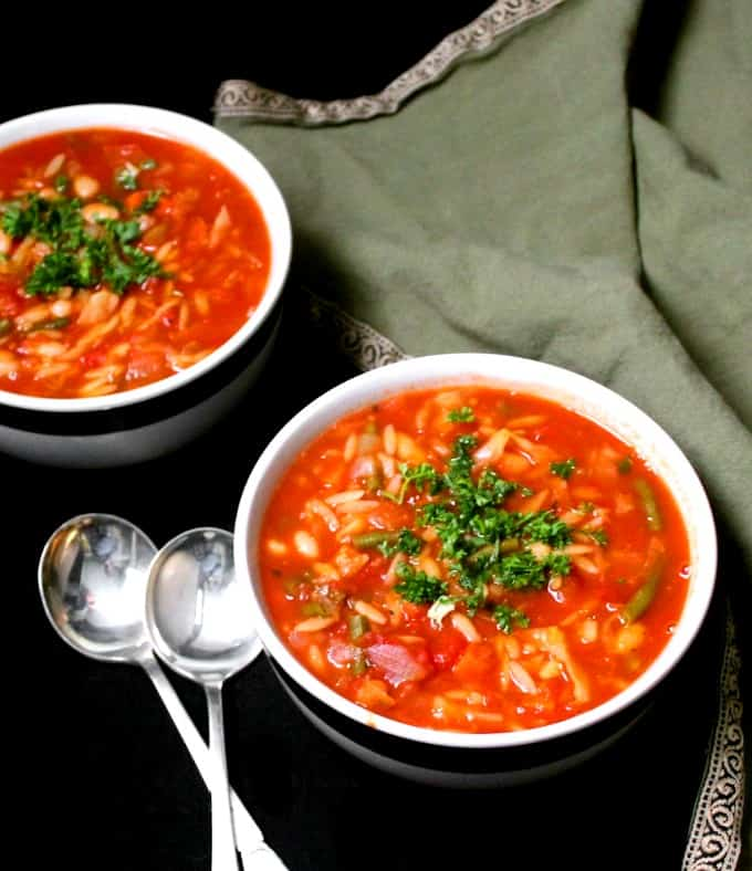 Two bowls of minestrone soup with two soup spoons and a green and gold napkin to the side.