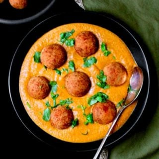 Vegan Malai Kofta Curry in a black bowl with cilantro sprinkled on top and golden kofta balls on the side against a green napkin
