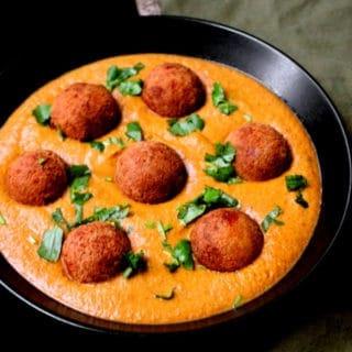 Malai Kofta Curry, a close up shot with golden brown tofu kofta balls in a creamy sauce