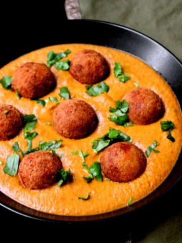 Malai Kofta Curry, a close up shot with golden brown tofu kofta balls in a creamy sauce