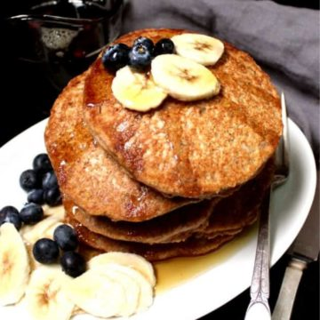 Photo of a stack of whole wheat vegan pancakes with blueberries and slices of banana and maple syrup
