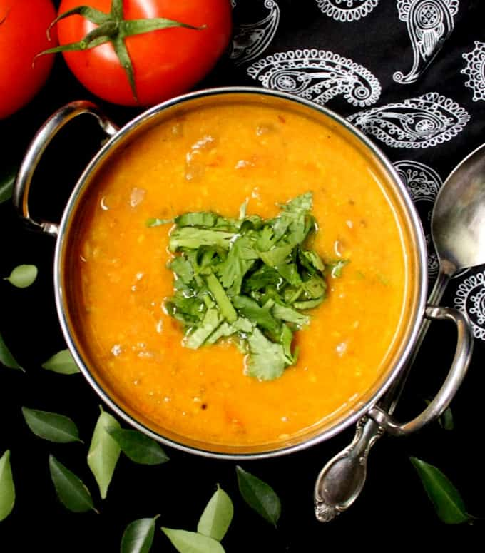 Indian tomato dal in a steel kadhai with a silver spoon and curry leaves