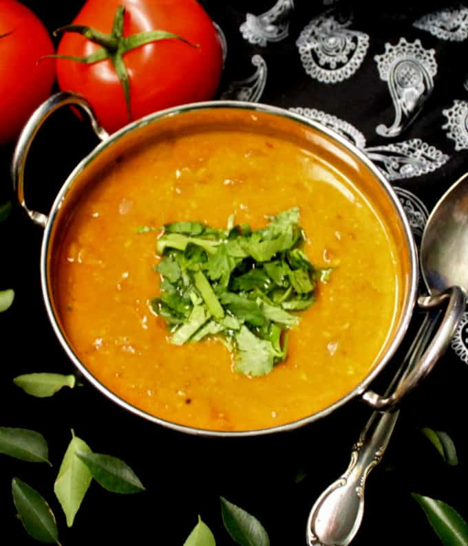 A front shot of easy tomato dal in a kadhai bowl with cilantro and curry leaves and a silver spoon