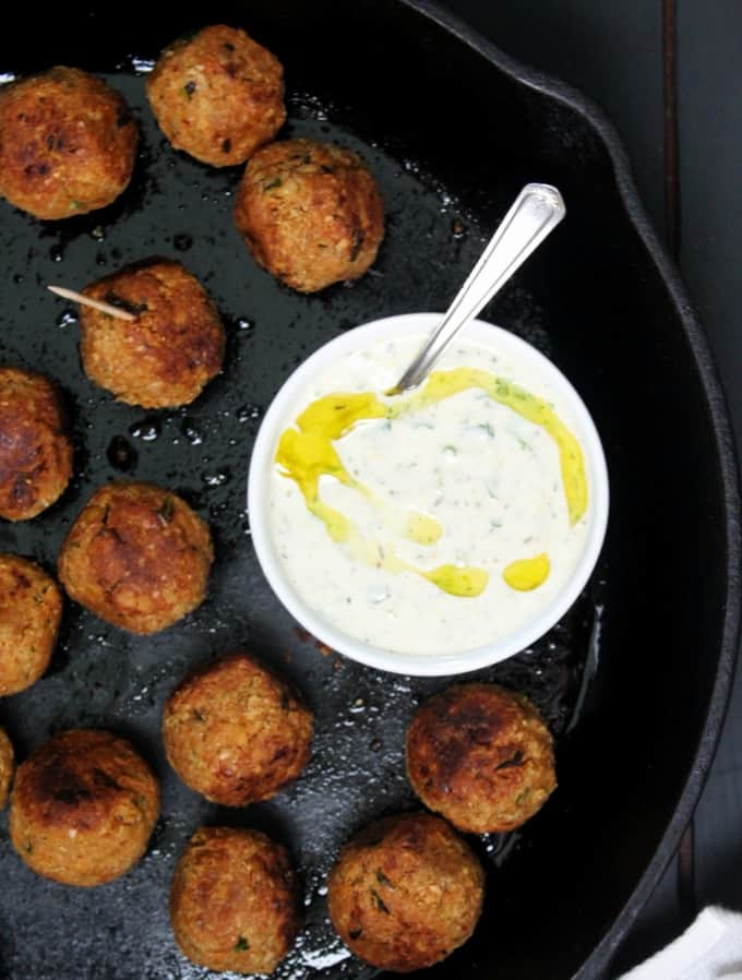 An overhead shot of vegan harissa meatballs with yogurt sauce in a white bowl