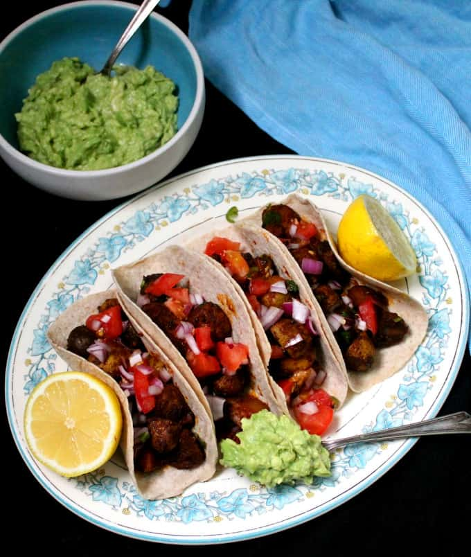 Close up shot of masala potato tacos in a blue and white platter with lemons, guac and salsa and a blue napkin