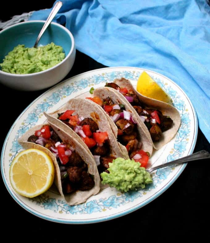 Overhead shot of four masala tacos with guacamole, salsa and lemons on a floral blue and white platter with a blue napkin