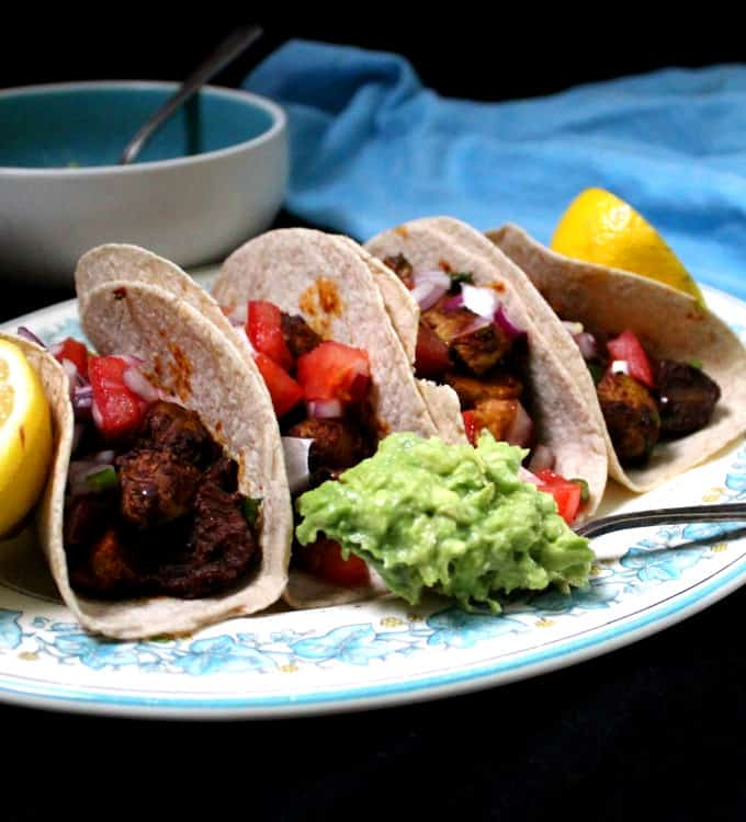 Closeup of vegan potato tacos with salsa, guacamole and limes on a blue and white platter.