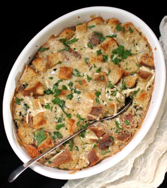 An overhead shot of a white, oval casserole dish with spinach, sausage and cheese casserole and a serving spoon on black background