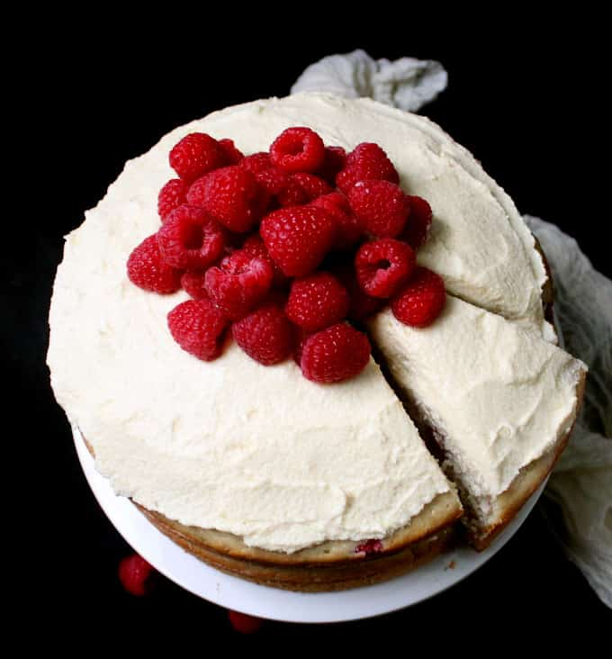 A white chocolate raspberry cake with a slice cut and partially moved on a white cake stand