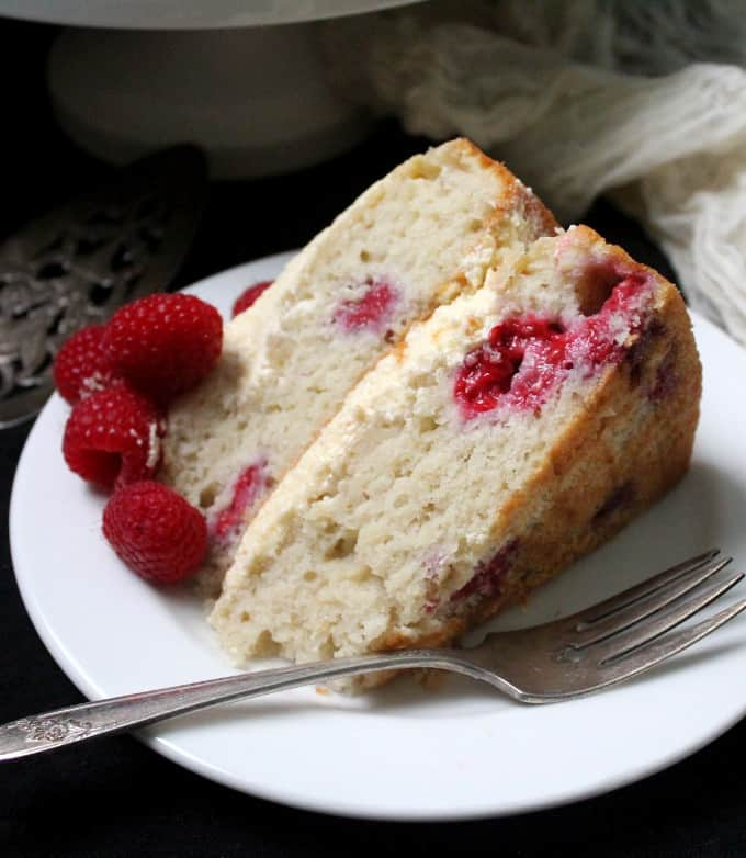 A fat slice of vegan white chocolate raspberry cake with a layer of buttercream in the middle and top on a white plate with a fork and fresh raspberries