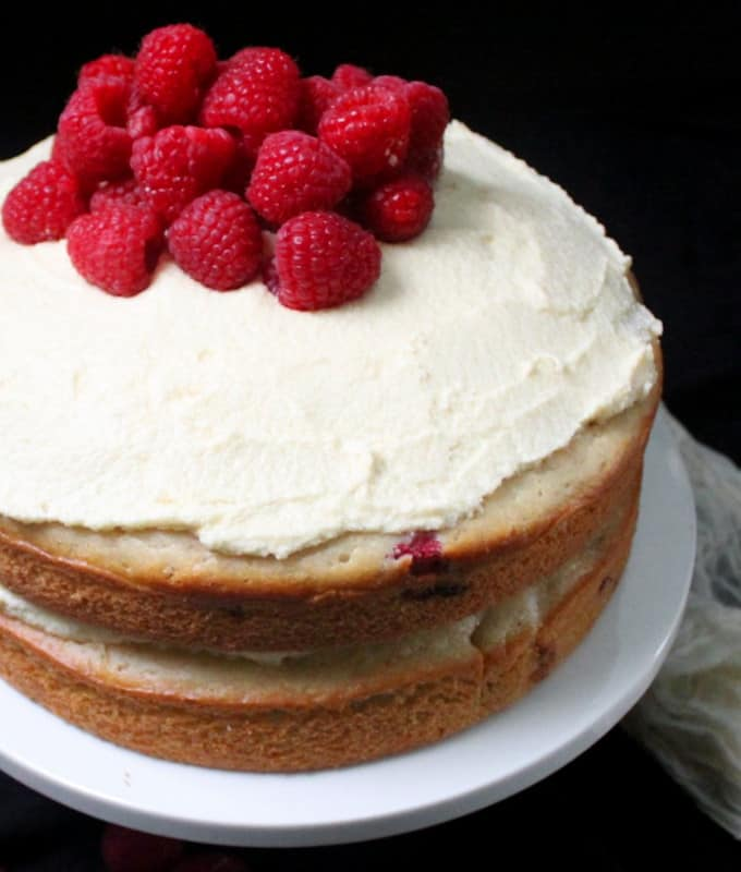 Close up of white chocolate raspberry cake with buttercream sandwiched between two layers of cake