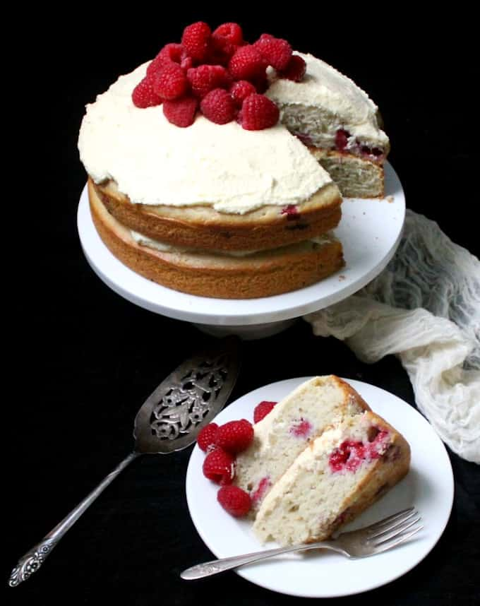 A front shot of a vegan white chocolate raspberry cake on a cake stand with a slice of the cake next to it on a white plate with a fork and a cake server