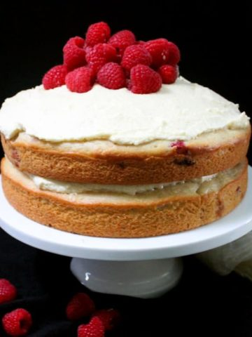 A front shot of a vegan white chocolate raspberry cake on a cake stand with fresh raspberries piled on top