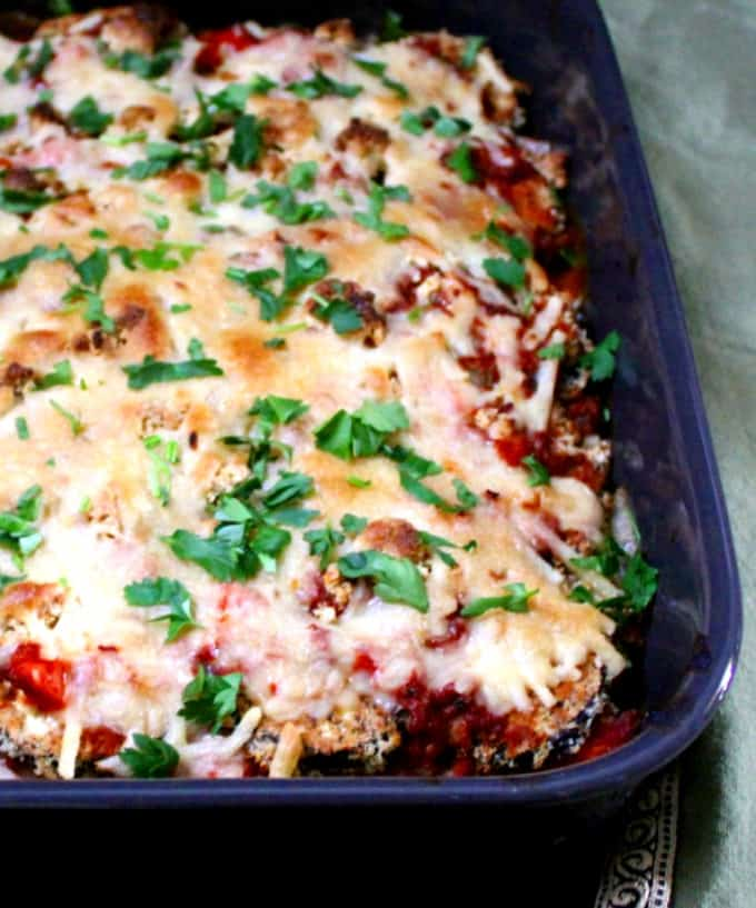 A close up of a baking dish with eggplant parm and a parsley garnish