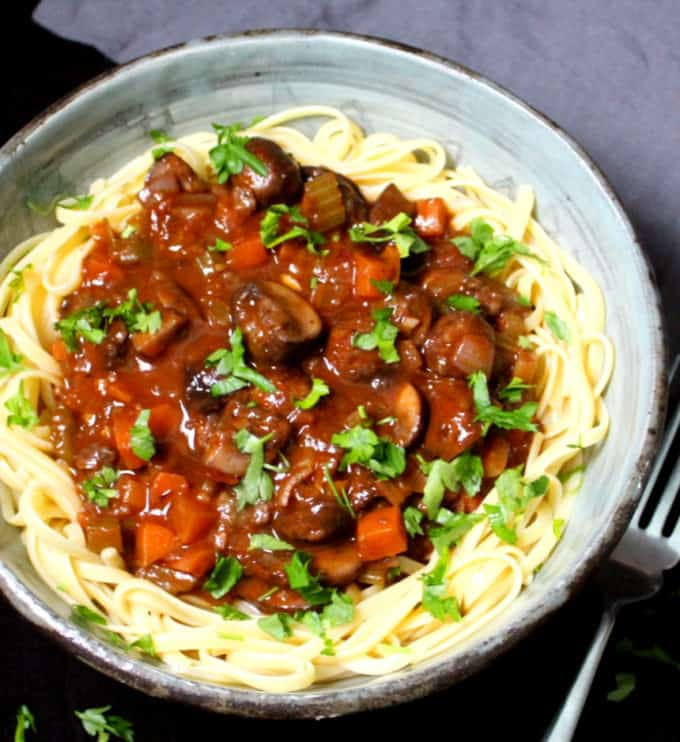 A partial front shot of a large bowl with vegan mushroom bourguignon and a fork