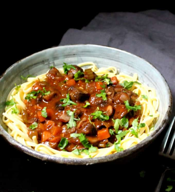 A front partial shot of a gray and blue hand-glazed bowl with vegan mushroom bourguignonne made with carrots, celery and onions on a bed of flat noodles with a fork on the side.
