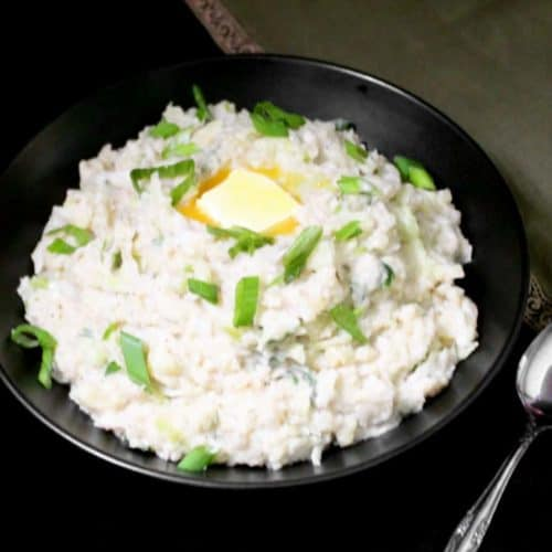 A bowl of vegan colcannon with a pat of vegan butter, scallions and a spoon and green napkin