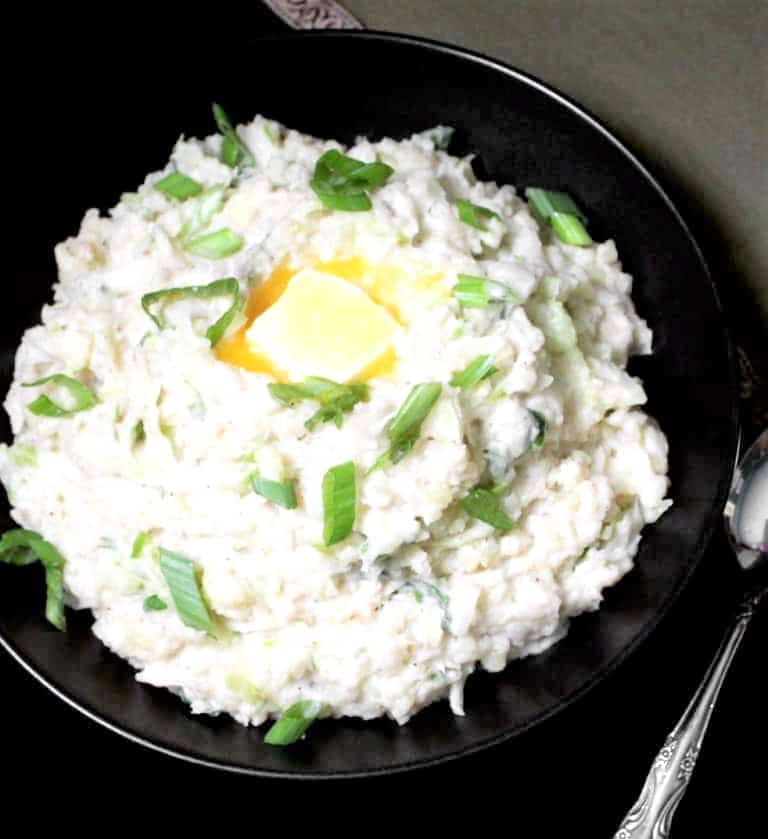Vegan Irish colcannon with sauerkraut in a black bowl with scallions, a spoon and green and gold napkin