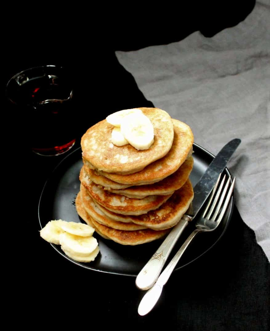 A stack of gluten-free, eggless pancakes on a black plate with maple syrup on the side, banana slices, a spoon, fork and gray napkin.