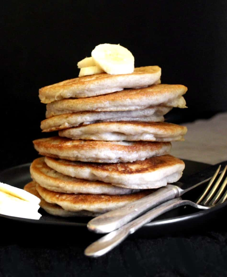 A stack of nine vegan gluten-free sourdough pancakes topped with bananas on a black plate.