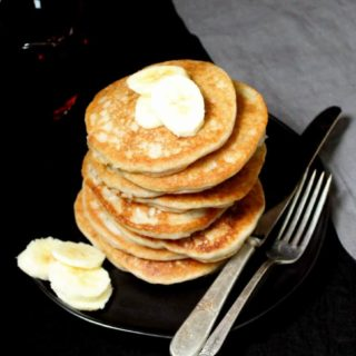 A stack of vegan gluten-free sourdough pancakes in a black plate with banana slices, a spoon, fork and gray napkin