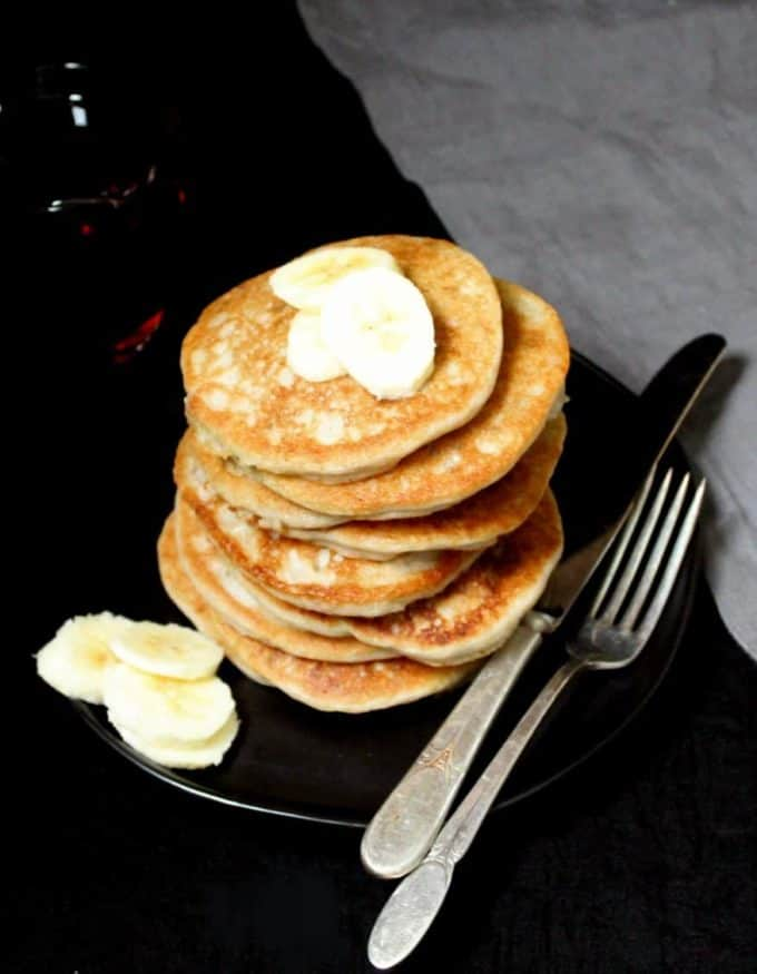 A stack of vegan gluten-free pancakes topped with bananas and with maple syrup on the side on a black plate with a knife and fork and a gray napkin.