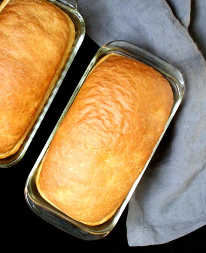 Two loaves of vegan sandwich bread in glass loaf pans with a gray napkin