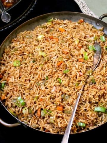 A large platter of veg fried rice with carrots, scallions and green peppers with a serving spoon and a vegetable dish on the side