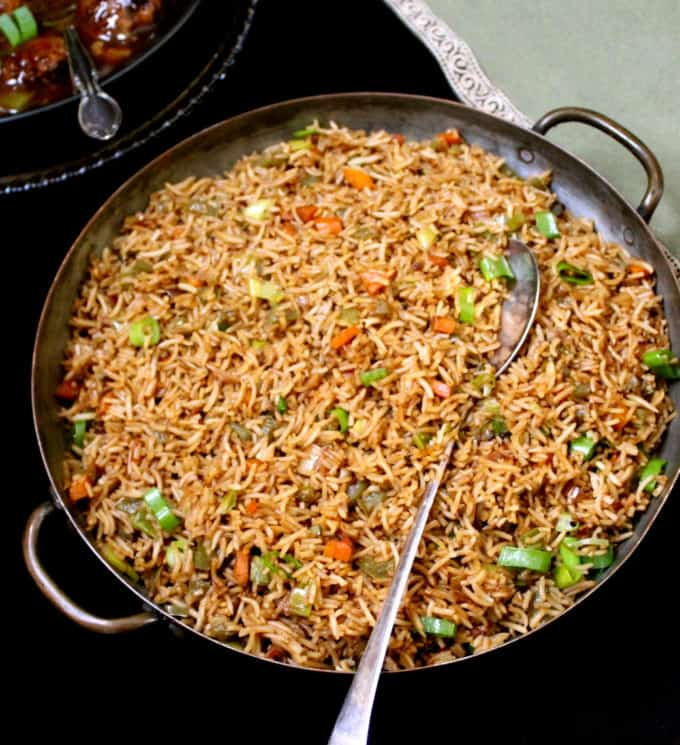 An overhead-front shot of a large copper server with Indo-Chinese veg fried rice