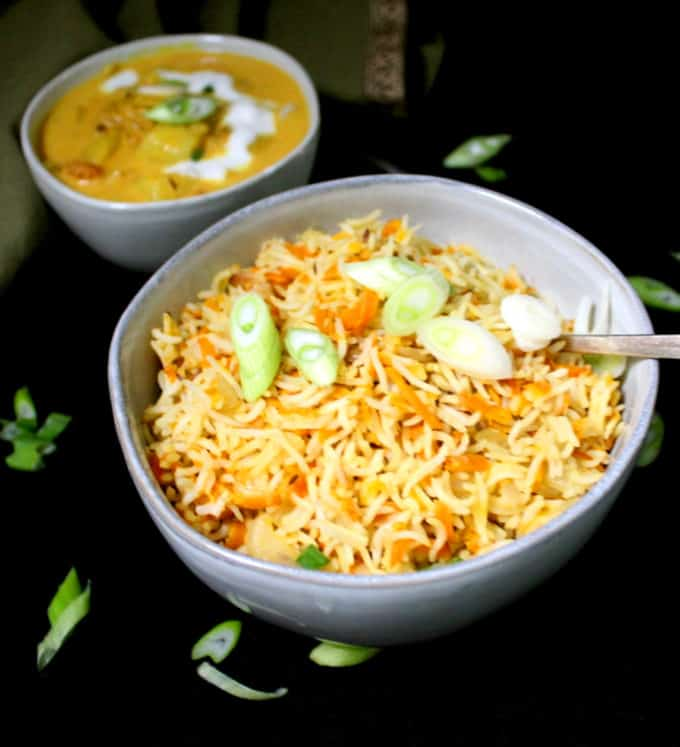 A bowl of carrot rice to be served with a coconut curry pictured in the background.