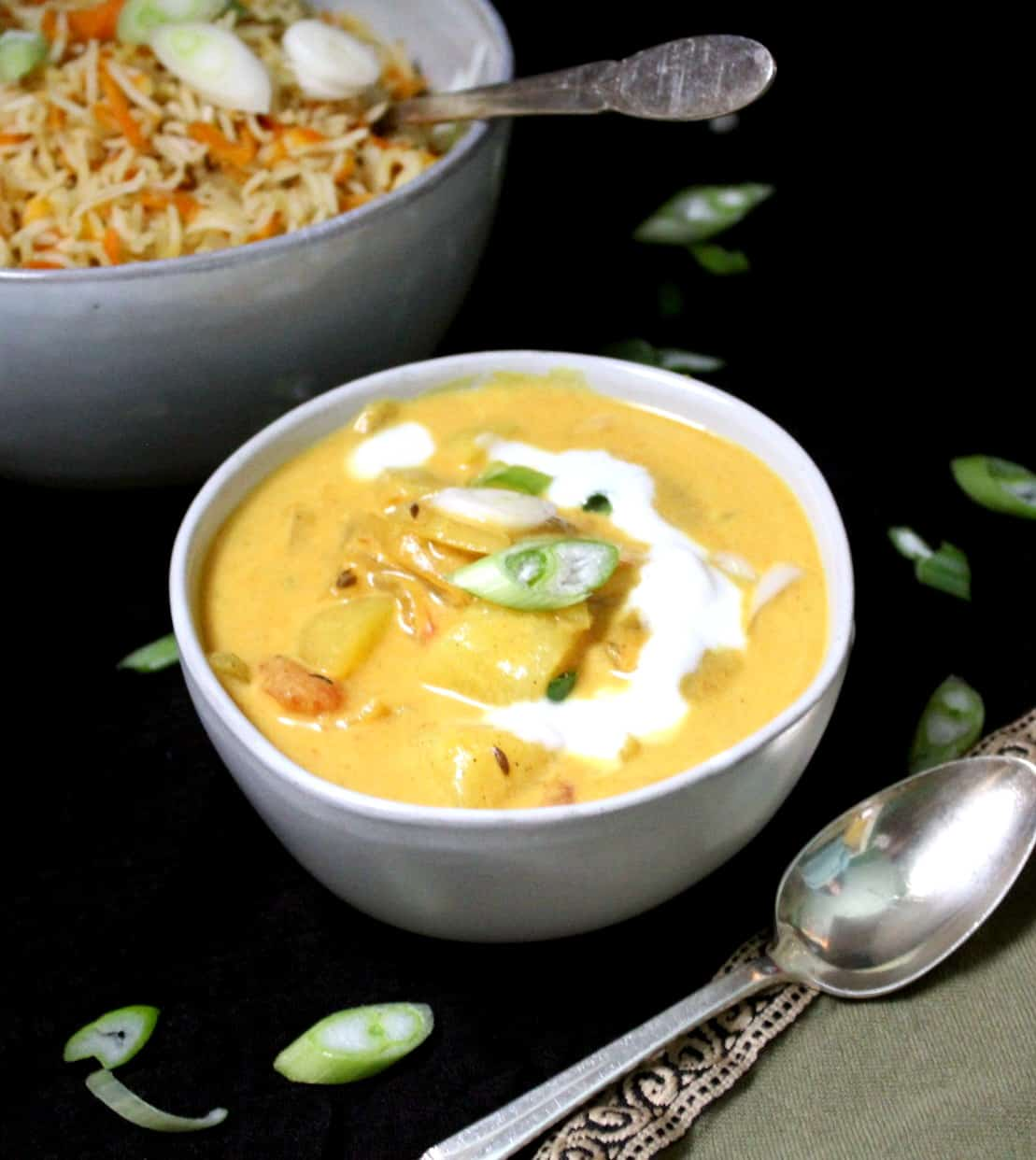 Coconut curry with tomatoes and potatoes in a ceramic bowl served with carrot rice and garnished with scallions.