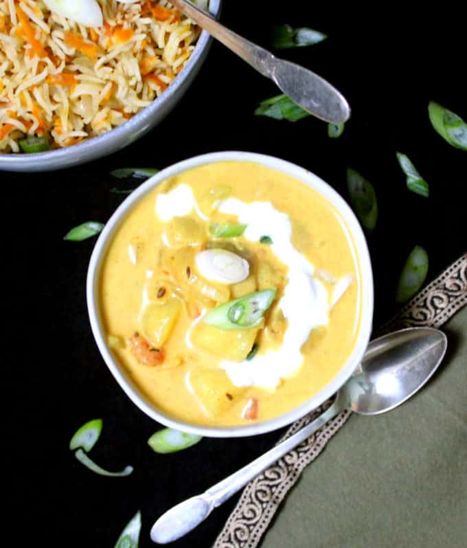 A top closeup shot of coconut curry in a ceramic bowl with scallions and carrot rice