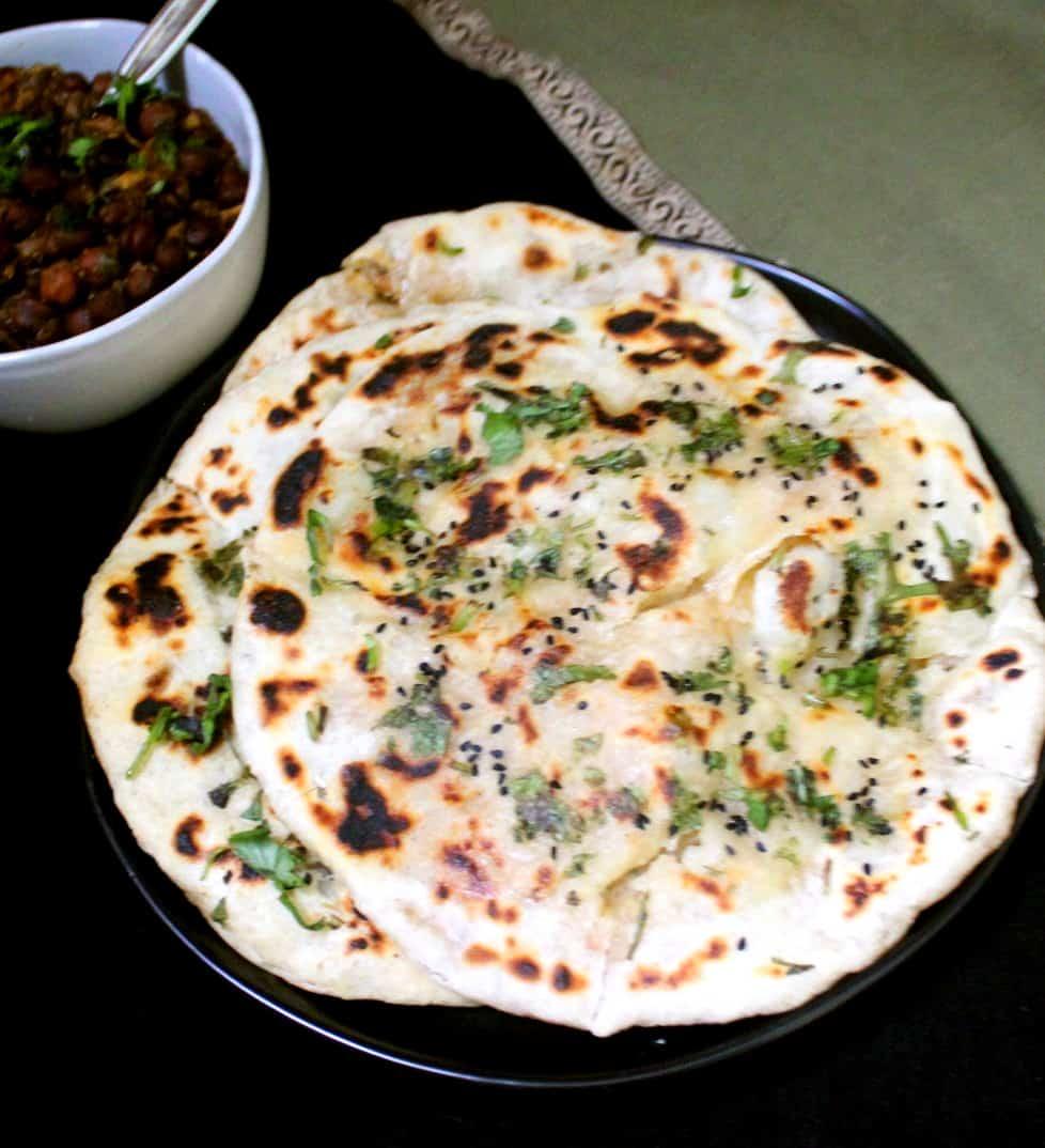 A top shot of three aloo kulcha with chana masala and a green and gold napkin
