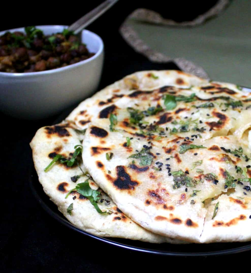 Partial shot of three aloo kulchas with chole in the background